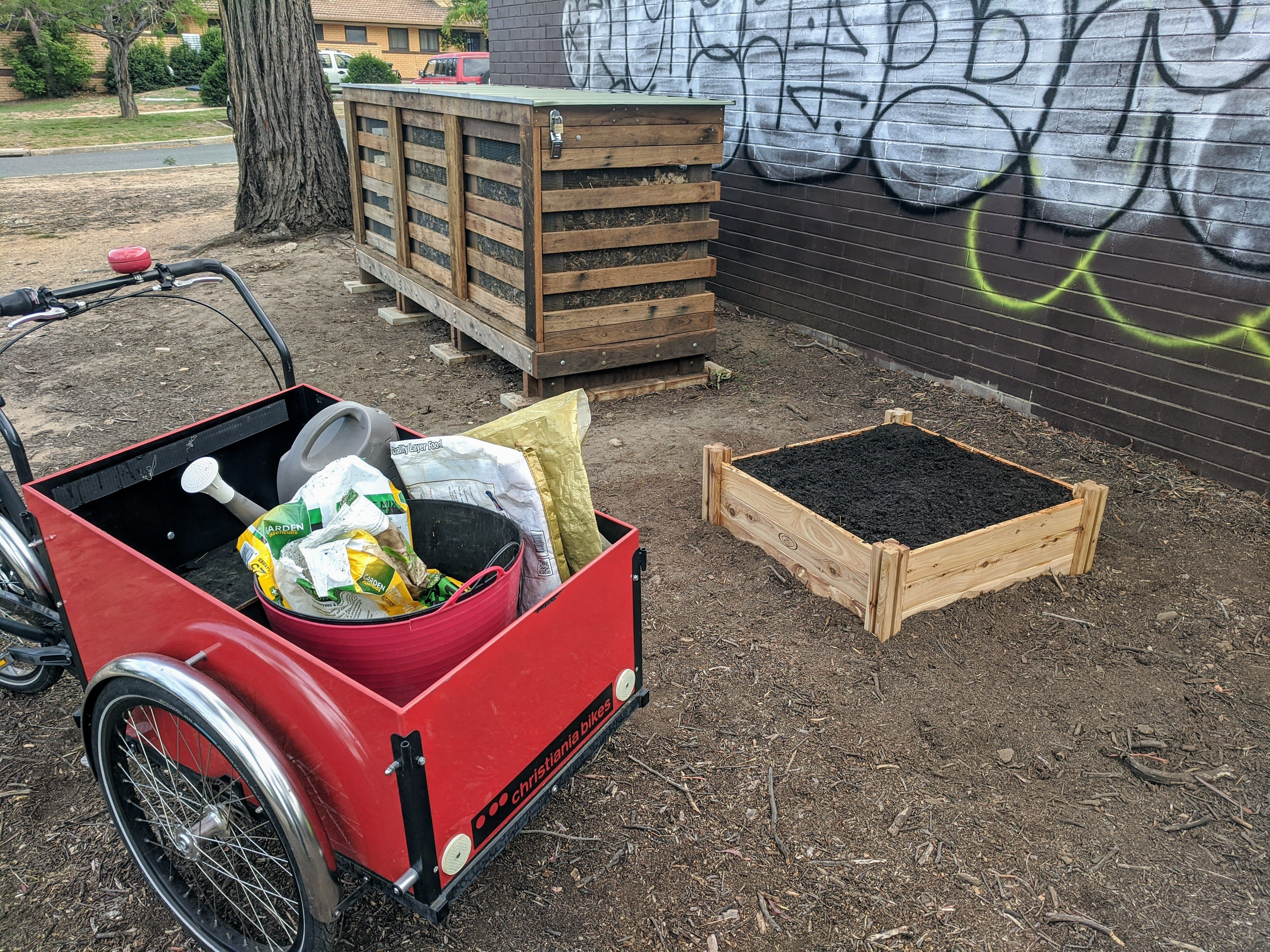 Wooden 3-bay composter, small garden bed, electric trike and tools